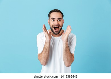 Image of excited young screaming happy bearded man posing isolated over blue wall background.