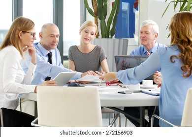 Image of executive sales woman presenting his idea to business people. Business women and businessman sitting around the conference desk and working on business plan. Teamwork with laptop and tablet.