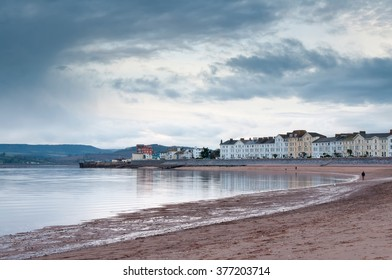 Image of Exmouth seafront, showing the beach and Georgian style houses, people walking in the distance. Taken late afternoon in the winter.