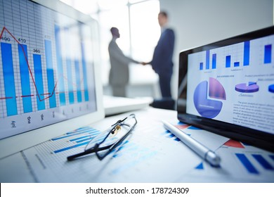 Image of eyeglasses, pen, two touchpads and financial documents at workplace with businessmen handshaking on background