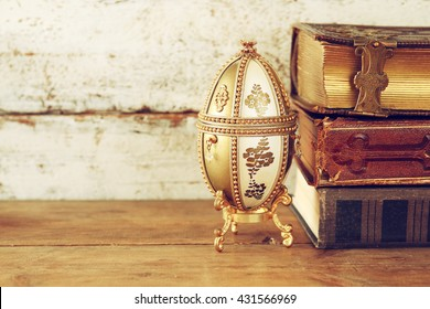 image of faberge egg and vintage books on wooden table. vintage filtered