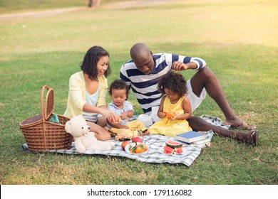 Image of a family having picnic outdoors