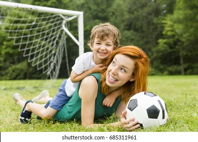 An Image of family, mother and son playing ball in the park