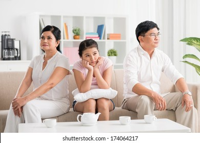 Image of a family where parents are in conflict while their daughter is boring and upset on the foreground