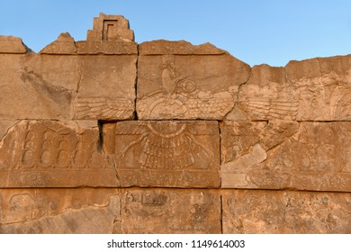 The image of faravahar - a winged sun, with the figure of Zarathustra. An ancient relief on the walls of the ruined Persepolis city. Iran.