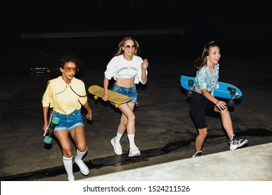 Image of fashion multiethnic girls in streetwear smiling and riding skateboards at night outdoors