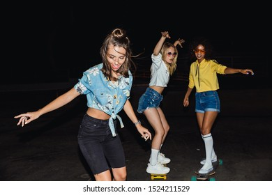 Image of fashion multinational girls in streetwear smiling and riding skateboards at night outdoors