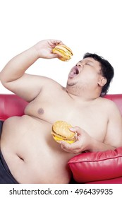 Image of fat man eating two big hamburgers on the red couch, isolated on the white background