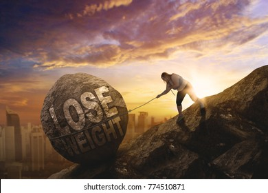 Image of fat woman pulling a text of lose weight in the stone with city background. Shot at sunset time