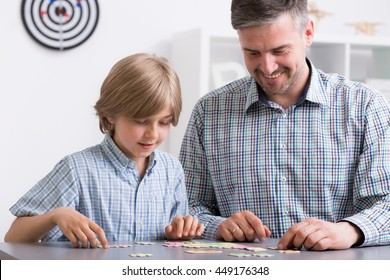 Image of father and son sitting beside desk doing puzzles