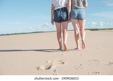 Image of female feet close-up on a beach background. Two women in shorts walk barefoot on the sand, leaving footprints.