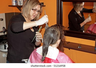 An image of a Female hair coloring at a salon
