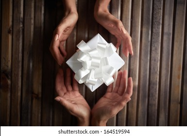 Image of female hands giving Christmas present to her friend