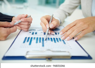 Image of female hands with pens during discussion of business documents at meeting