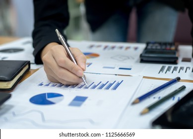 Image of female hands with pens over business document at meeting Banking business or financial analyst desktop accounting charts, pens indicates in the graphics