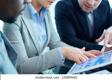 Image of female pointing at touchscreen during discussion of business document at meeting