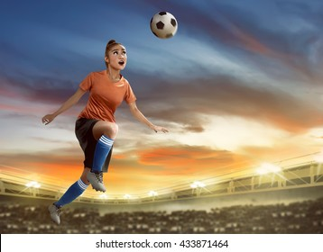 Image of female soccer player heading ball on the field