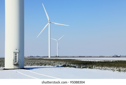 Image of a field with wind turbines during the winter.