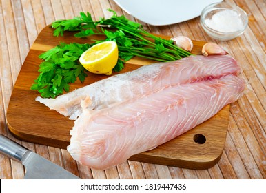 Image of fillet of raw perch fillet before cooking with greens on wooden background