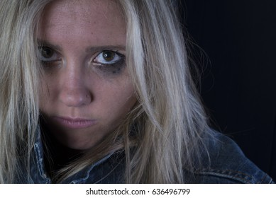 Image of a filthy homeless girl on black background.