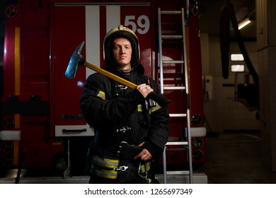 Image of fireman in protective helmet with hammer on background of fire truck