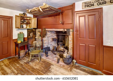 An image of the fireplace in a primitive colonial style reproduction home.  The home was built prior to the American Revolutionary war, and this room contains many antiques from the late 18th century.