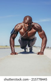Image of fit young guy doing push-ups. Young fitness model exercising outdoors.