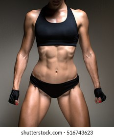Image of fitness woman in sports clothing looking down. Young female model with muscular body.