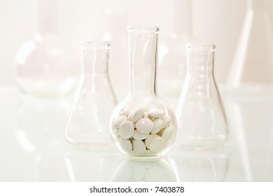 Image of flask with tablets on the background of different glass jars