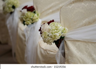 An image of floral arrangements located on seats at a wedding ceremony
