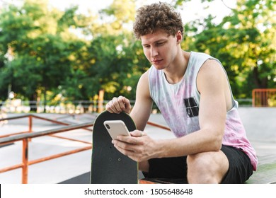 Image of focused handsome man in streetwear sitting with skateboard and using cellphone at summer skate park