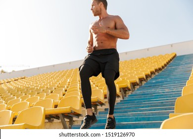 Image of focused shirtless sportsman running by empty stadium seats while doing workout outdoors