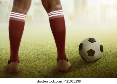 Image of football player feet with ball on the field