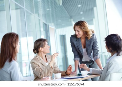Image of four businesswomen interacting at meeting