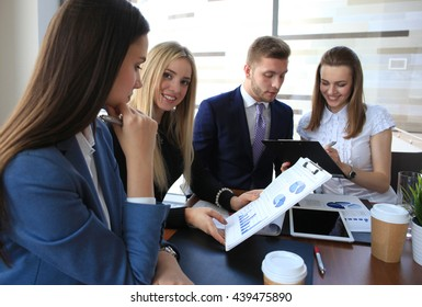 Image of four successful businesswomen looking at camera at meeting