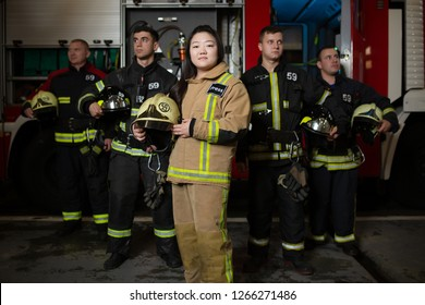 Image of four young male and female firefighters on background of fire truck