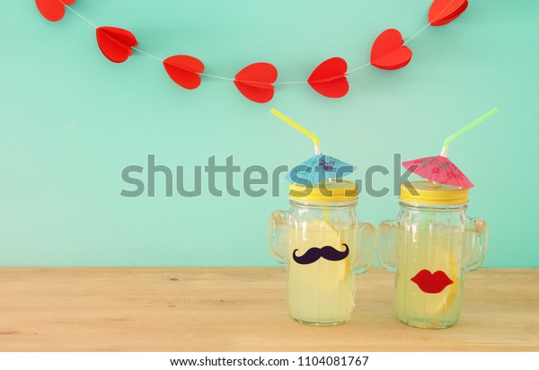 Image of fresh lemonade drink in cute cactus shape glasses wearing mustache and lips, over wooden table. Tropical summer romantic vacation concept