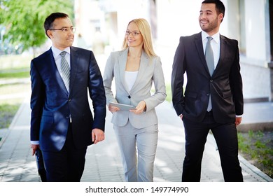 Image of friendly business team walking down street and talking