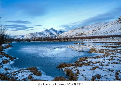 Image of frozen lake in front of mountain cover with snow