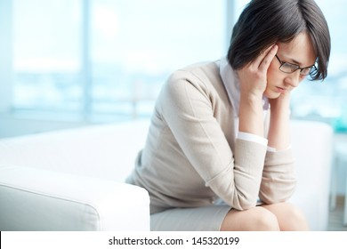Image of a frustrated or tired young brunette rubbing temples