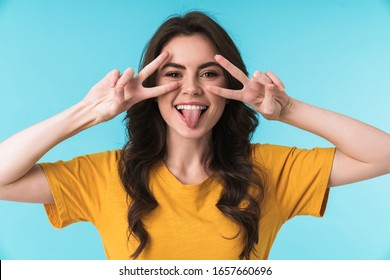 Image of a funny cheery young pretty woman posing isolated over blue wall background showing peace gesture and tongue.