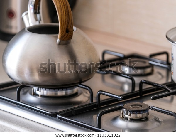 The image of a gas stove close up with kettle and pan