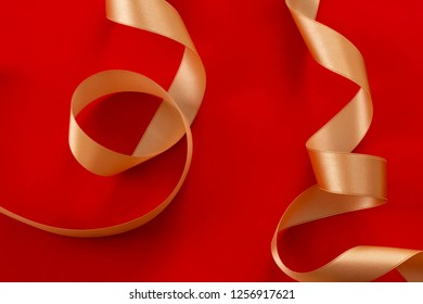 An image of gifts of a gold ribbon with a red solid background