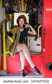 Image of ginger firewoman in helmet looking in camera sitting in cab of fire engine