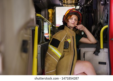 Image of ginger firewoman looking in camera sitting in cab of fire engine