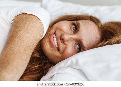 Image of ginger happy woman with freckles smiling at camera while lying in bed at home