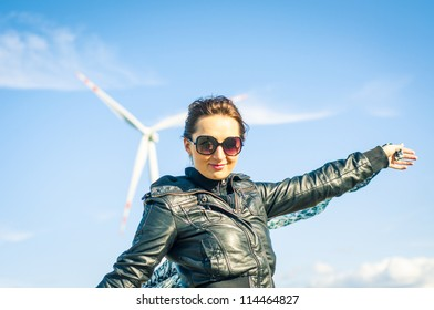 An image of girl holding canvas-cape and windturbine in background