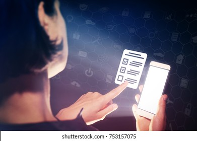 Image of a girl with a smartphone in hands. She presses on the  questionnaire icon. Concept of online testing, questionnaires, voting.