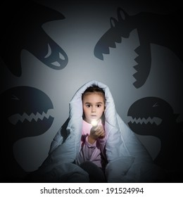 image of a girl under the covers with a flashlight the night afraid of ghosts