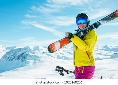 Image of girl wearing helmet, mask with skis on her shoulder